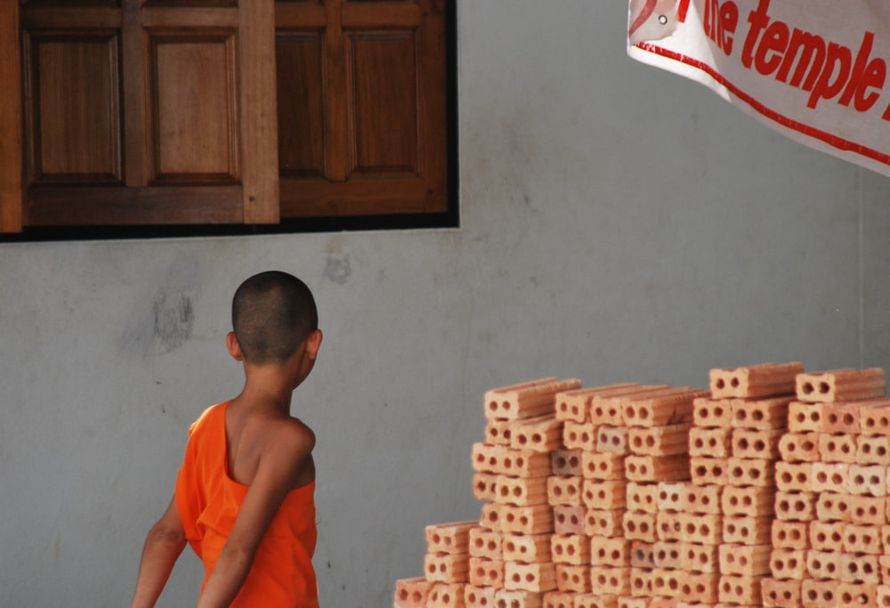 boy walking near white painted wall