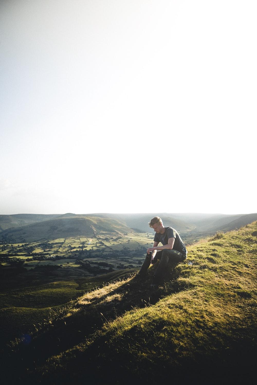 man sitting on green grass ground