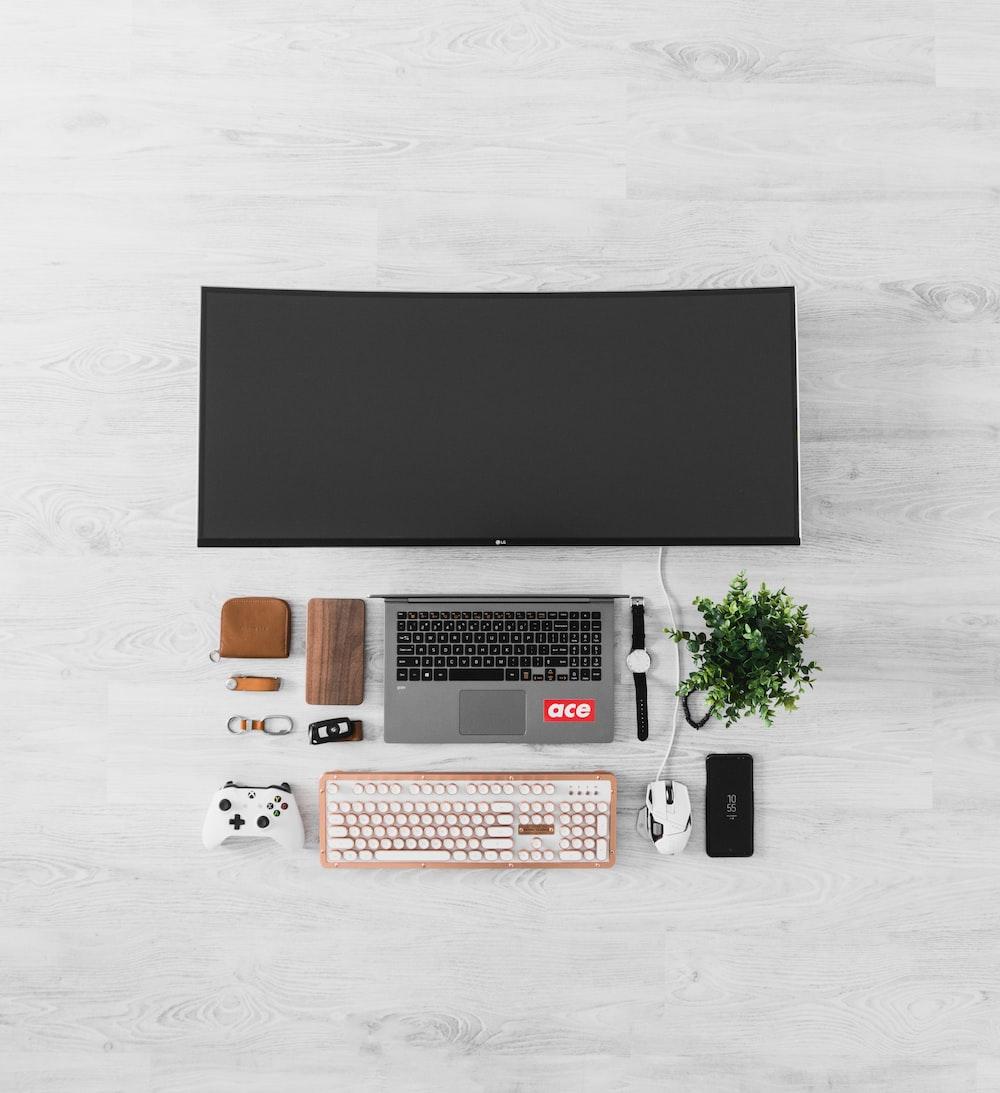 black flat screen TV and gray laptop computer