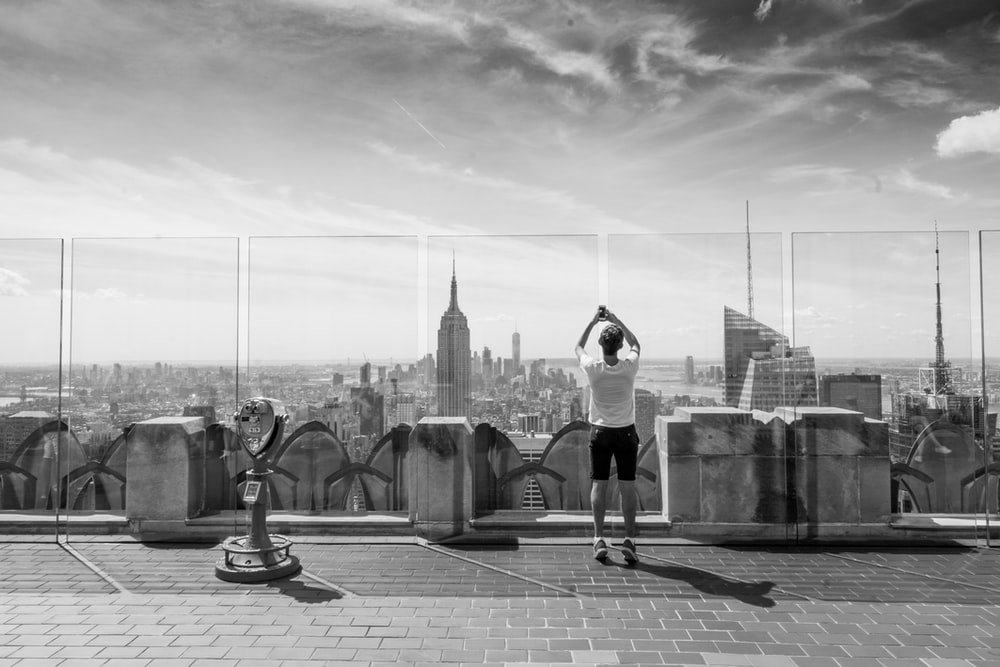 grayscale photography of man standing near tower viewer