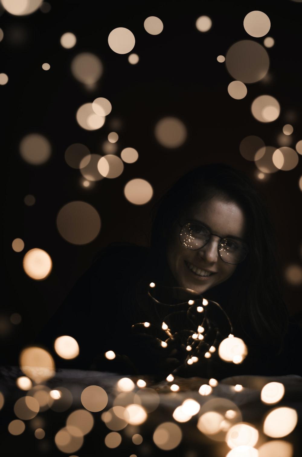 bokeh photography of woman wearing black shirt and black framed eyeglasses