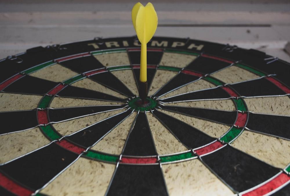 yellow dart pin on bullseye dart board