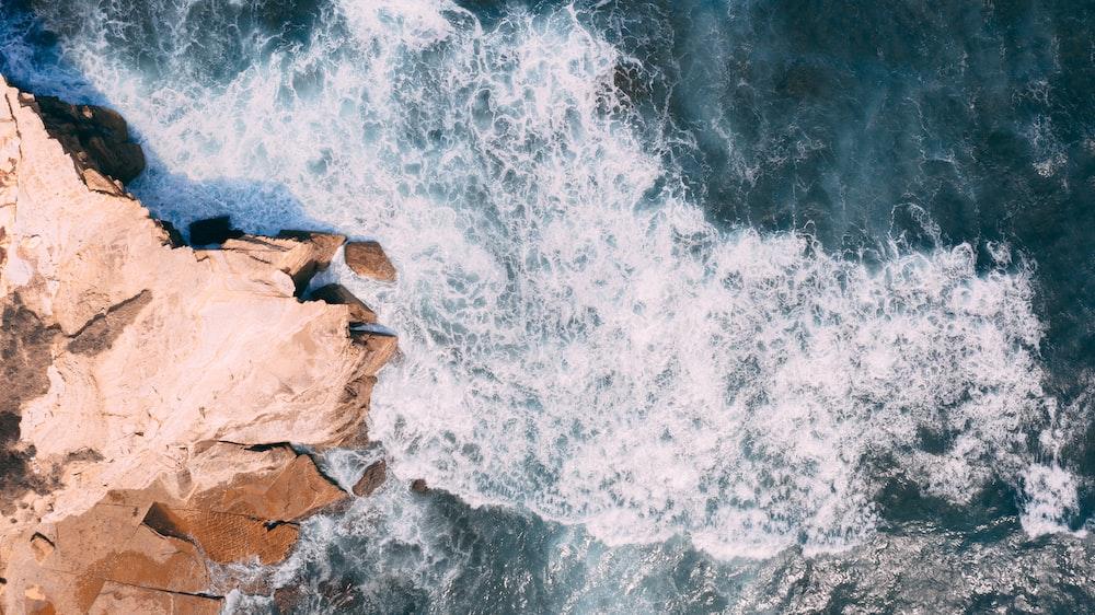 waves crashing on rocks during daytime