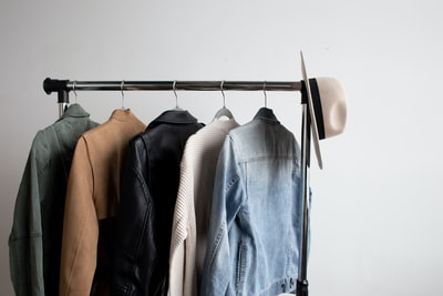one cowboy hat and five jackets hanged on clothes rack style teams background