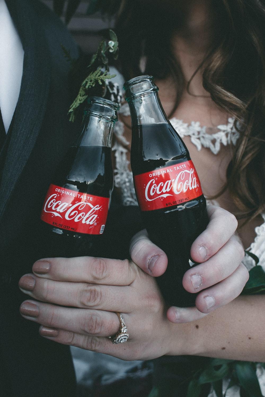 two Coca-Cola soda bottles