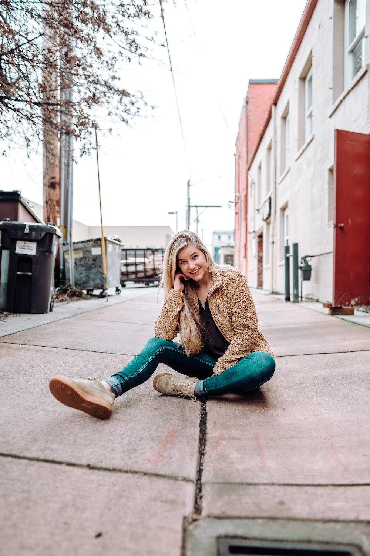 woman sitting on sidewalk