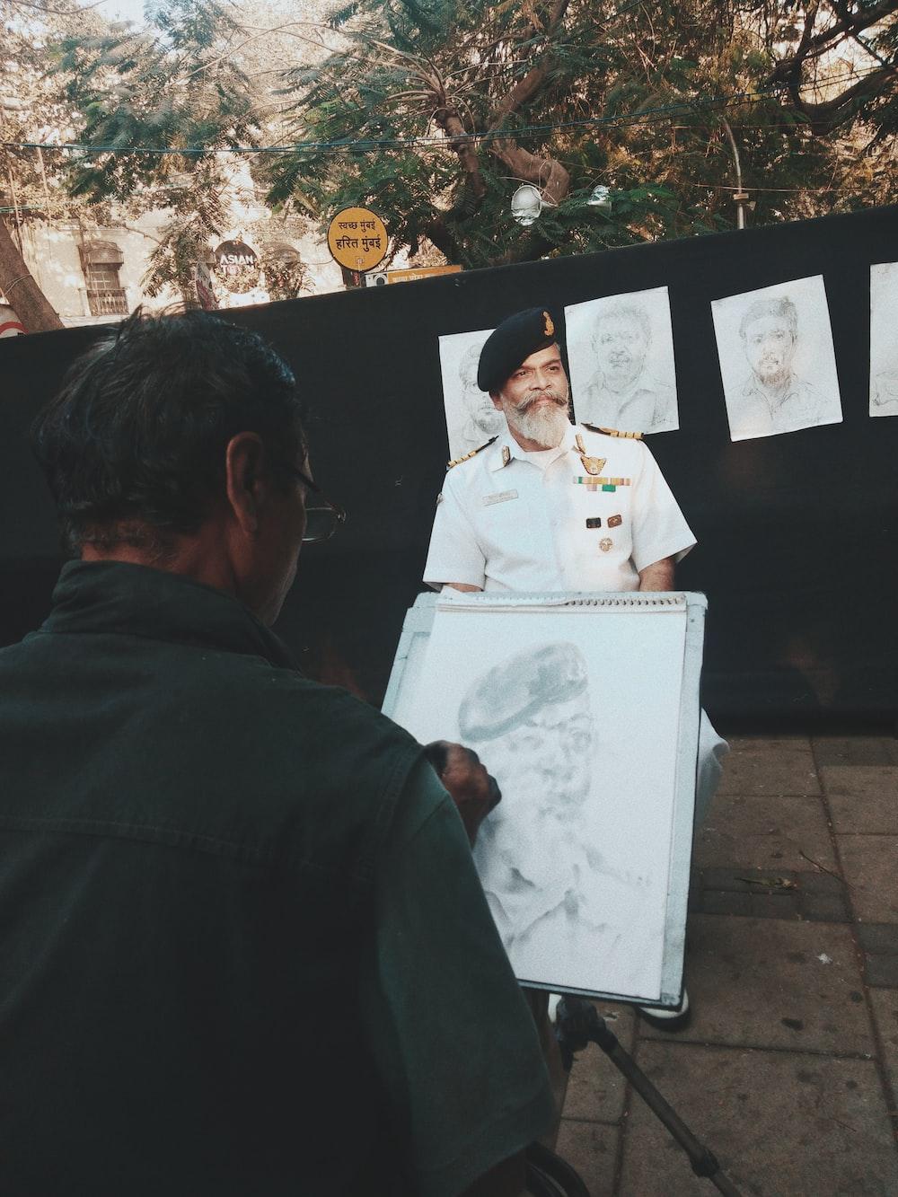 man sketching man sitting down