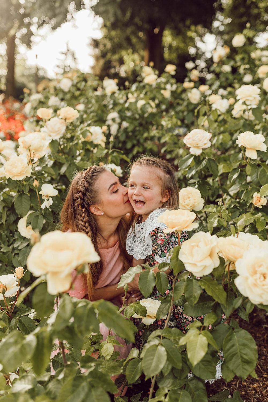 woman kissing girl's cheek between white roses garden