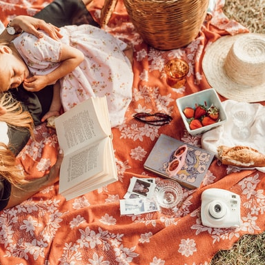 woman reading with girl while lying on orange and white floral picnic mat