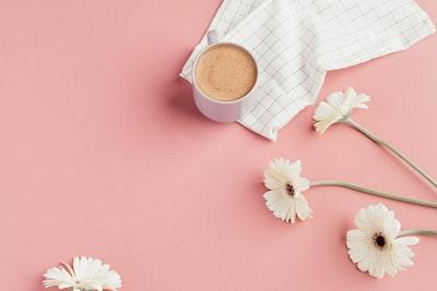 white ceramic mug near white flowers pastel zoom background