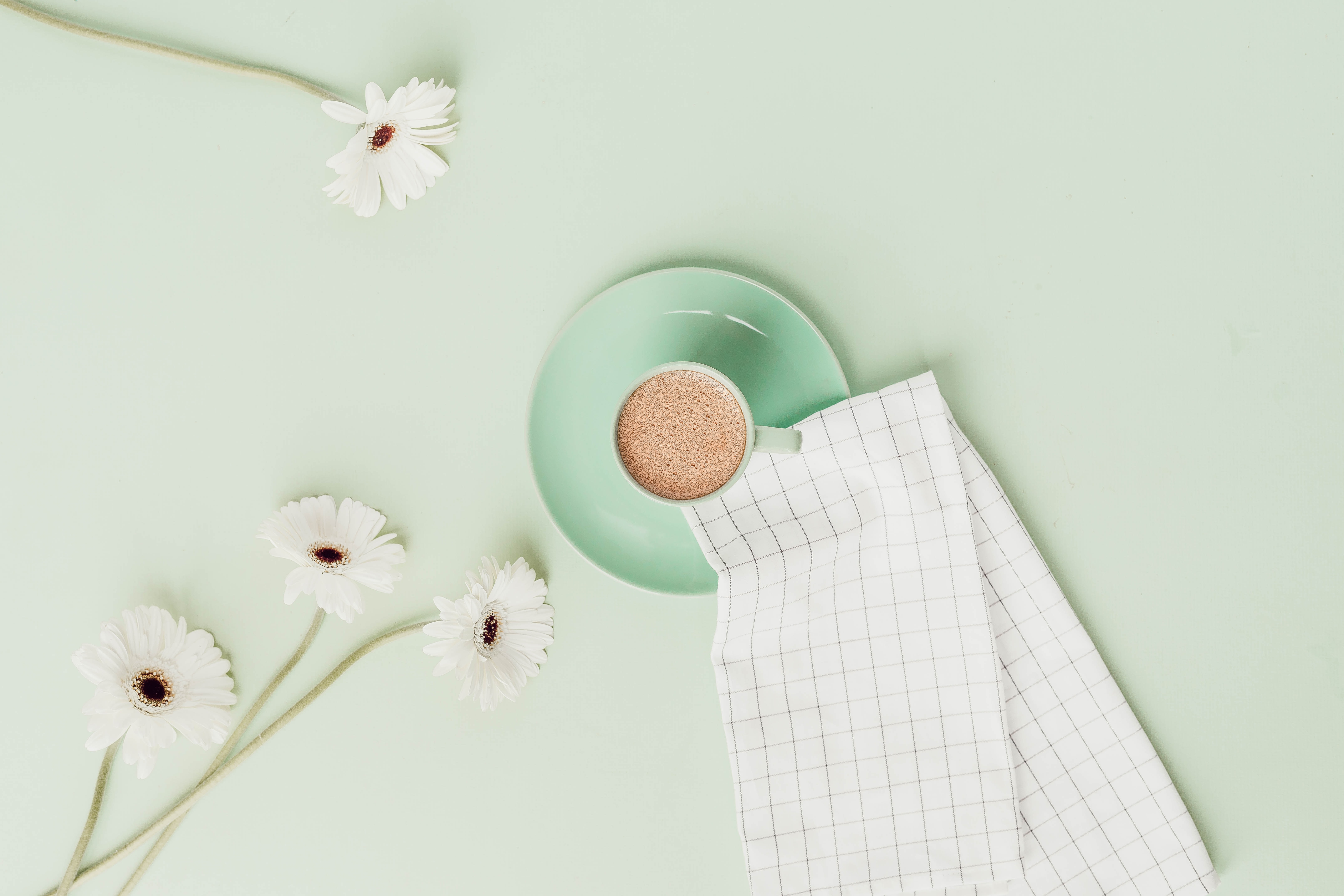 cup of beverage with daisies