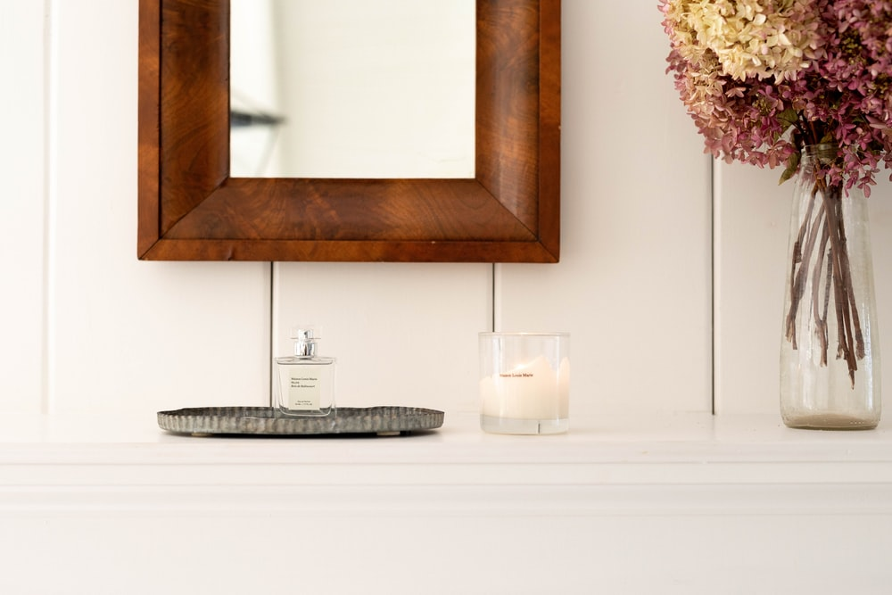 white candle beside clear glass flower vase