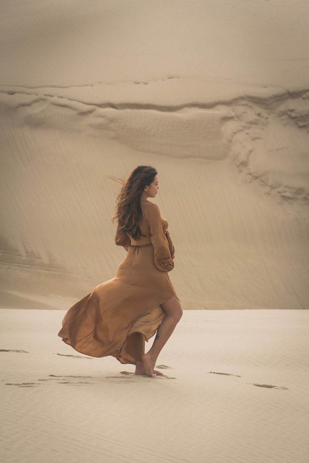woman walking on sand during day