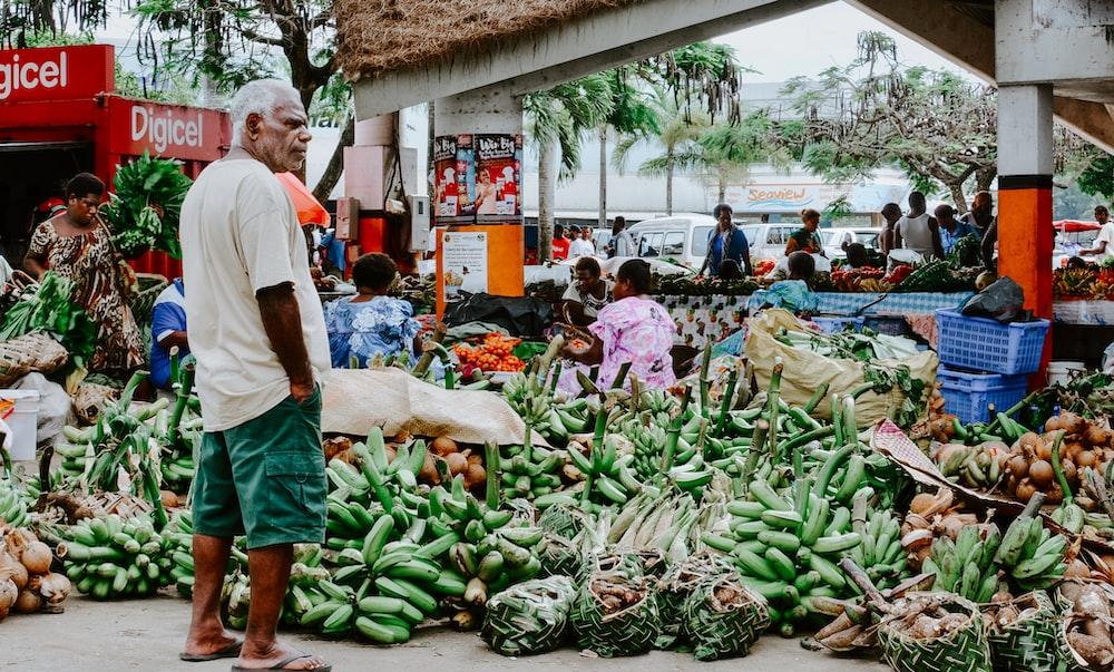 man standing in front of bananas