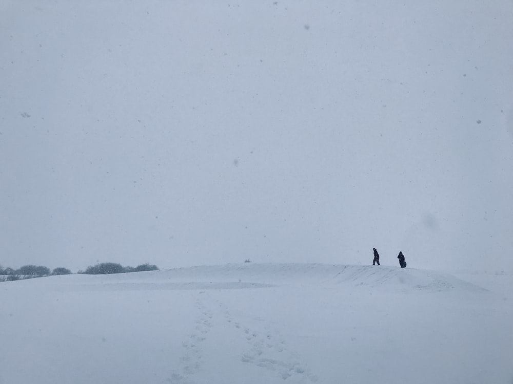 silhouette of two people on snowy land