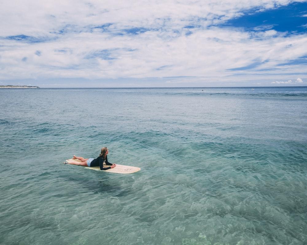 woman lying on surfboard