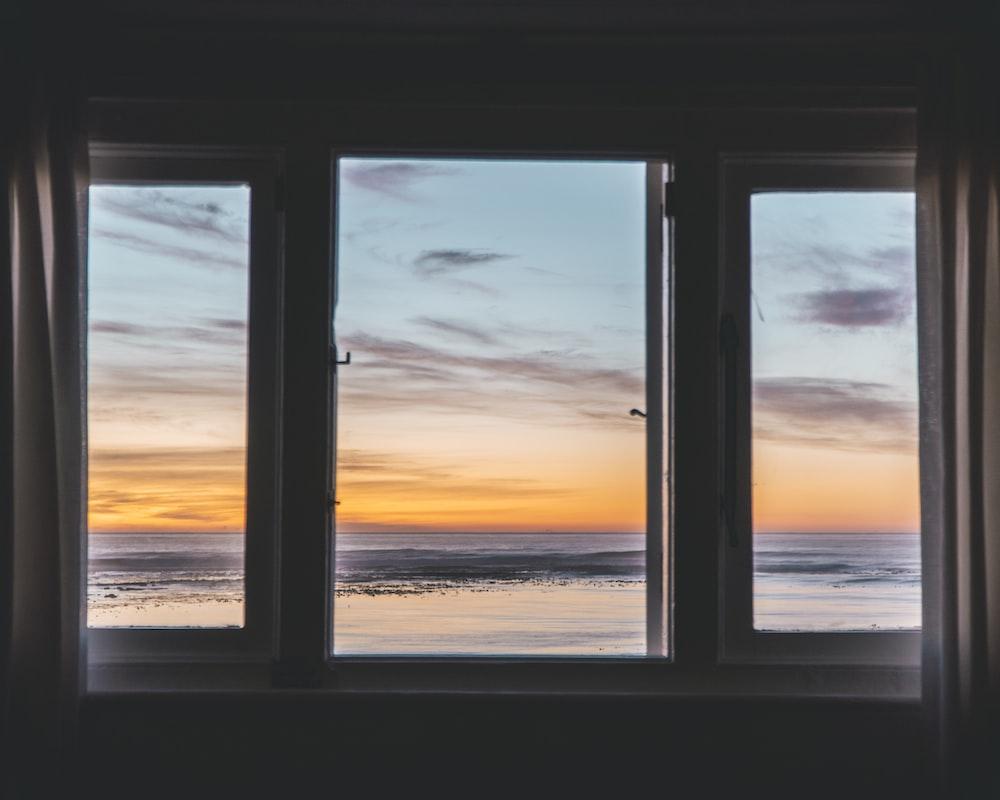white wooden framed glass window near body of water