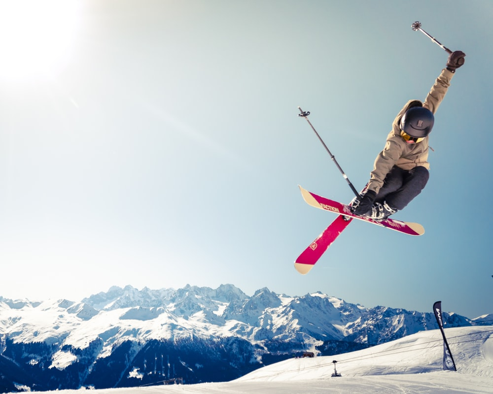 person in brown jacket doing snow ski blade trick