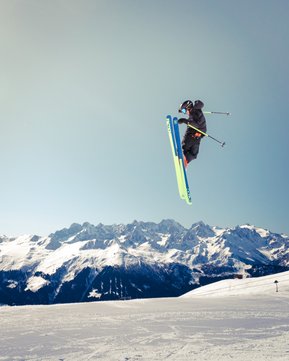 person jumping with skis and ski poles above snowfield