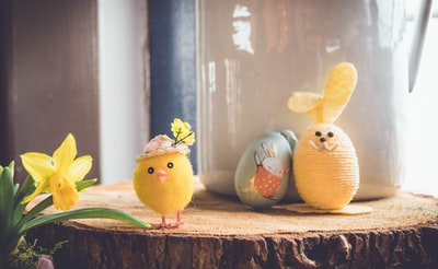 yellow bird plush toy on brown wood easter zoom background