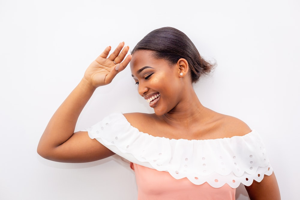 smiling woman wearing white and pink off-shoulder dress