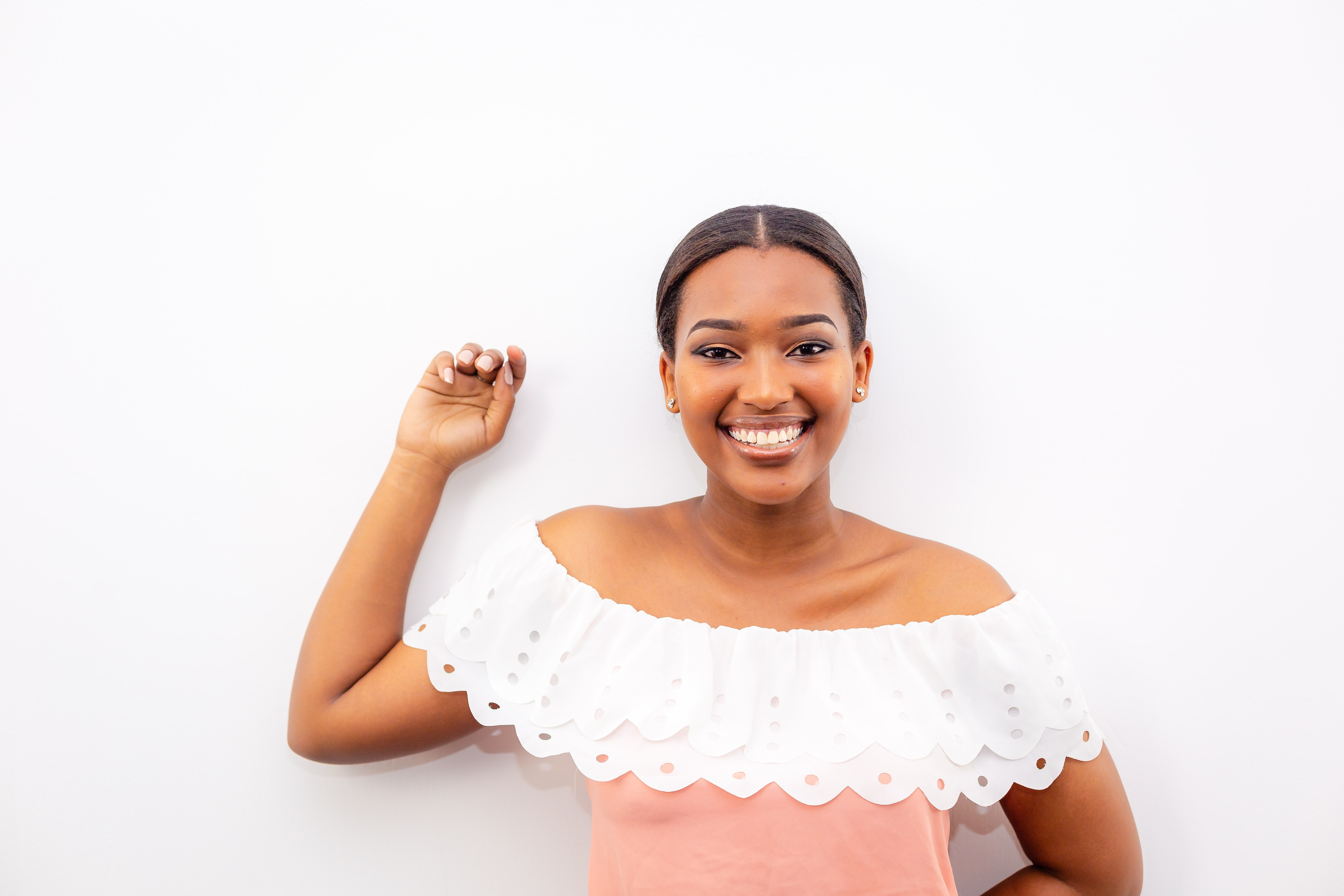 woman in white and pink off-shoulder top standing beside wall