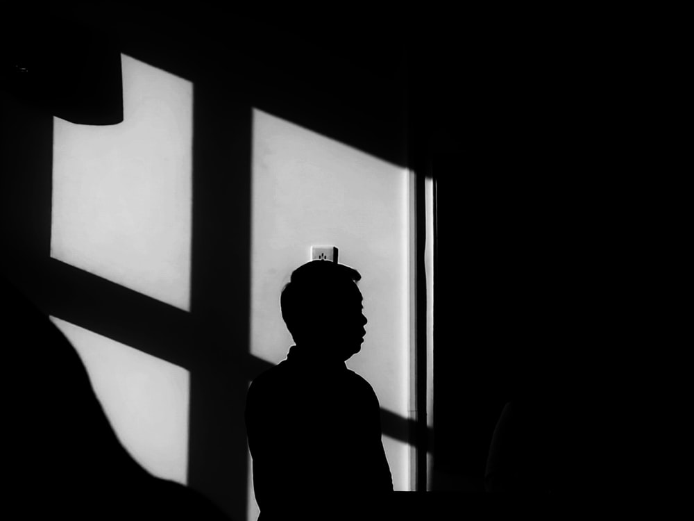 silhouette of person across wall switch