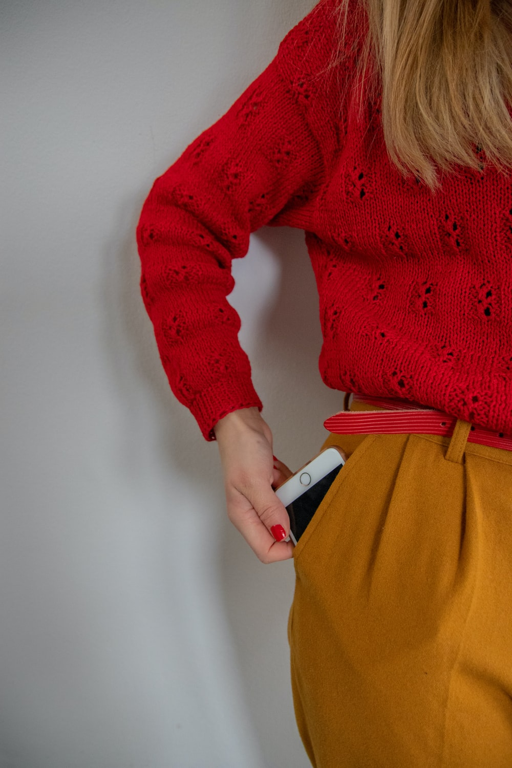 woman standing while holding gold iPhone