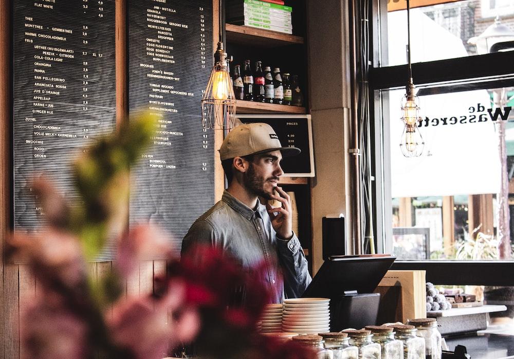 man wearing brown cap in across menu board