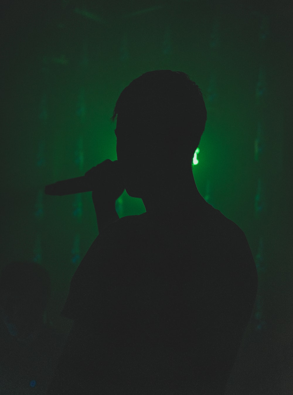 silhouette of person holding microphone