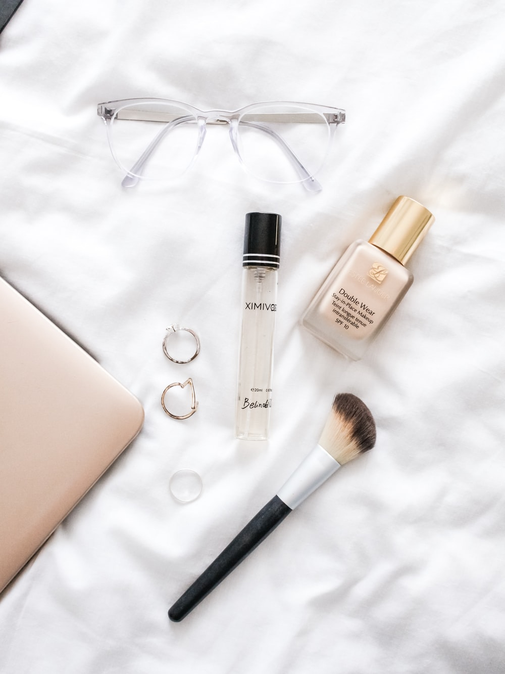 clear glass fragrance bottle and black makeup brush on white textile