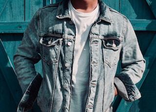 man standing beside blue wooden wall