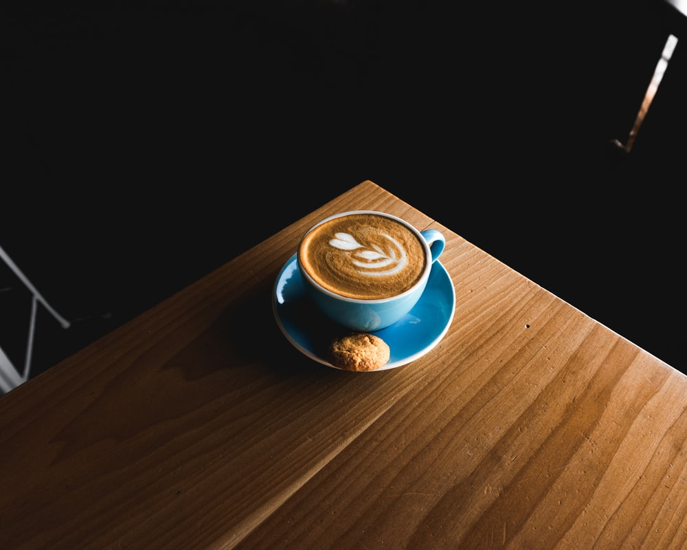 blue ceramic teacup on brown wooden surface