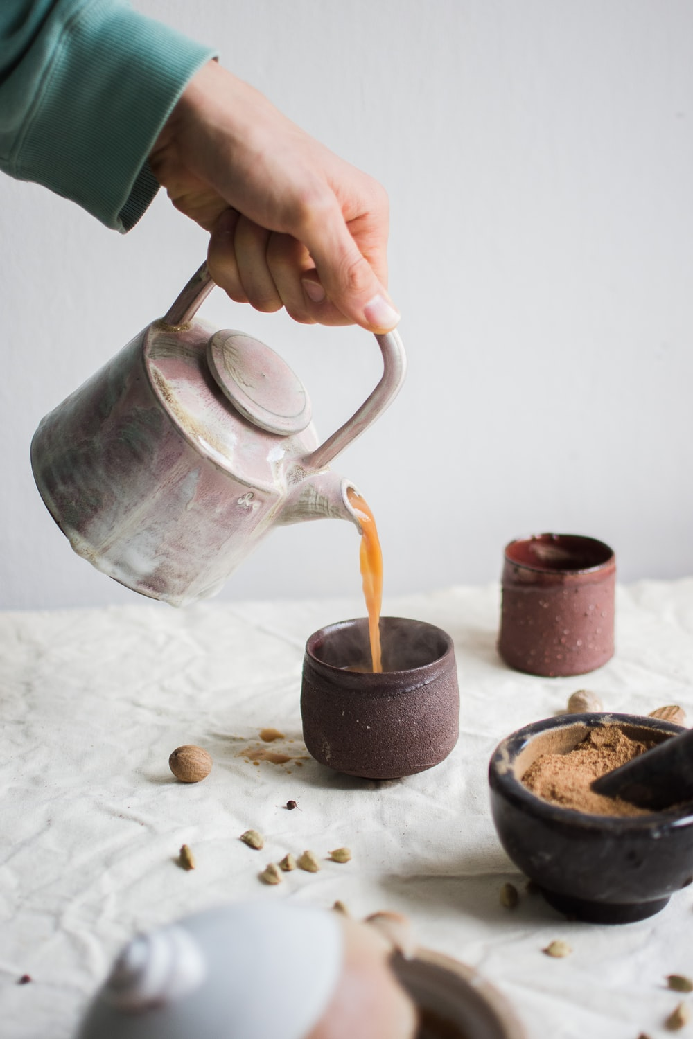 person pouring coffee on brown cup
