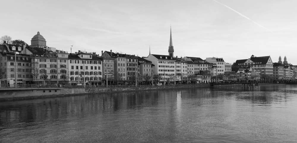 grayscale photo of buildings beside body of water
