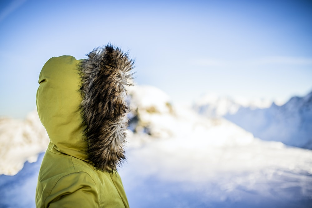 person wearing green and brown parka jacket