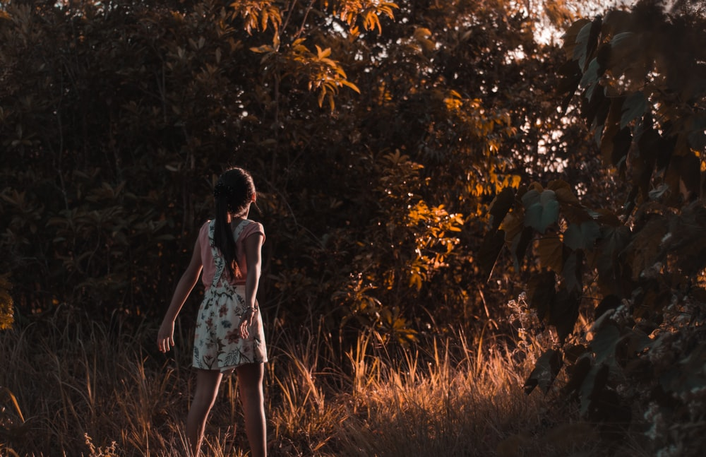 girl walking on brown grass near trees during daytime