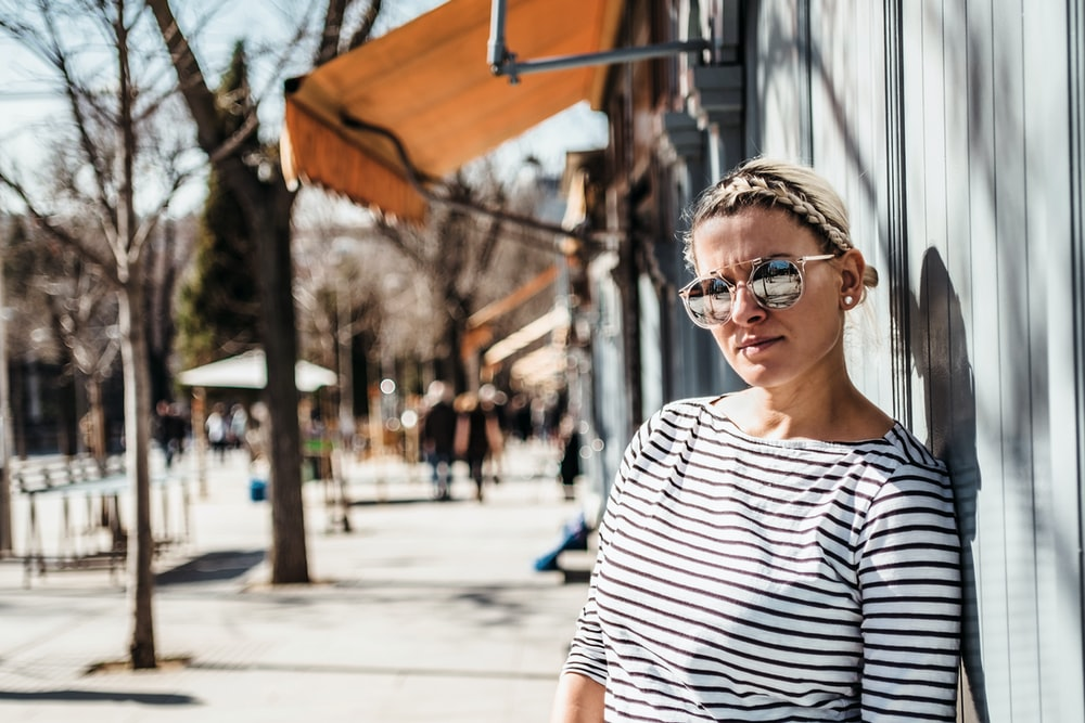 woman leaning on wall wearing sunglasses and striped shirt