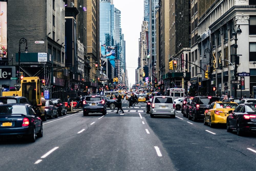 vehicles on road between buildings