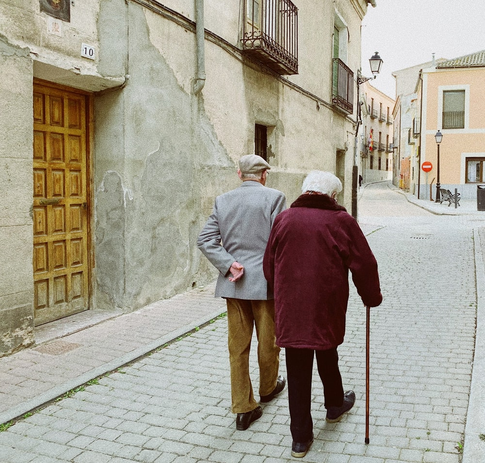 man and woman walking near closed wooden door