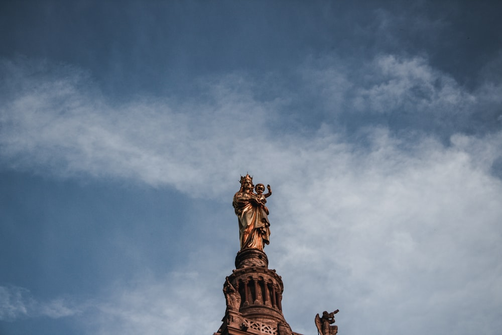 man carrying boy statue under blue and white sky