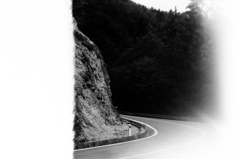 black and white photography of grey concrete curved road