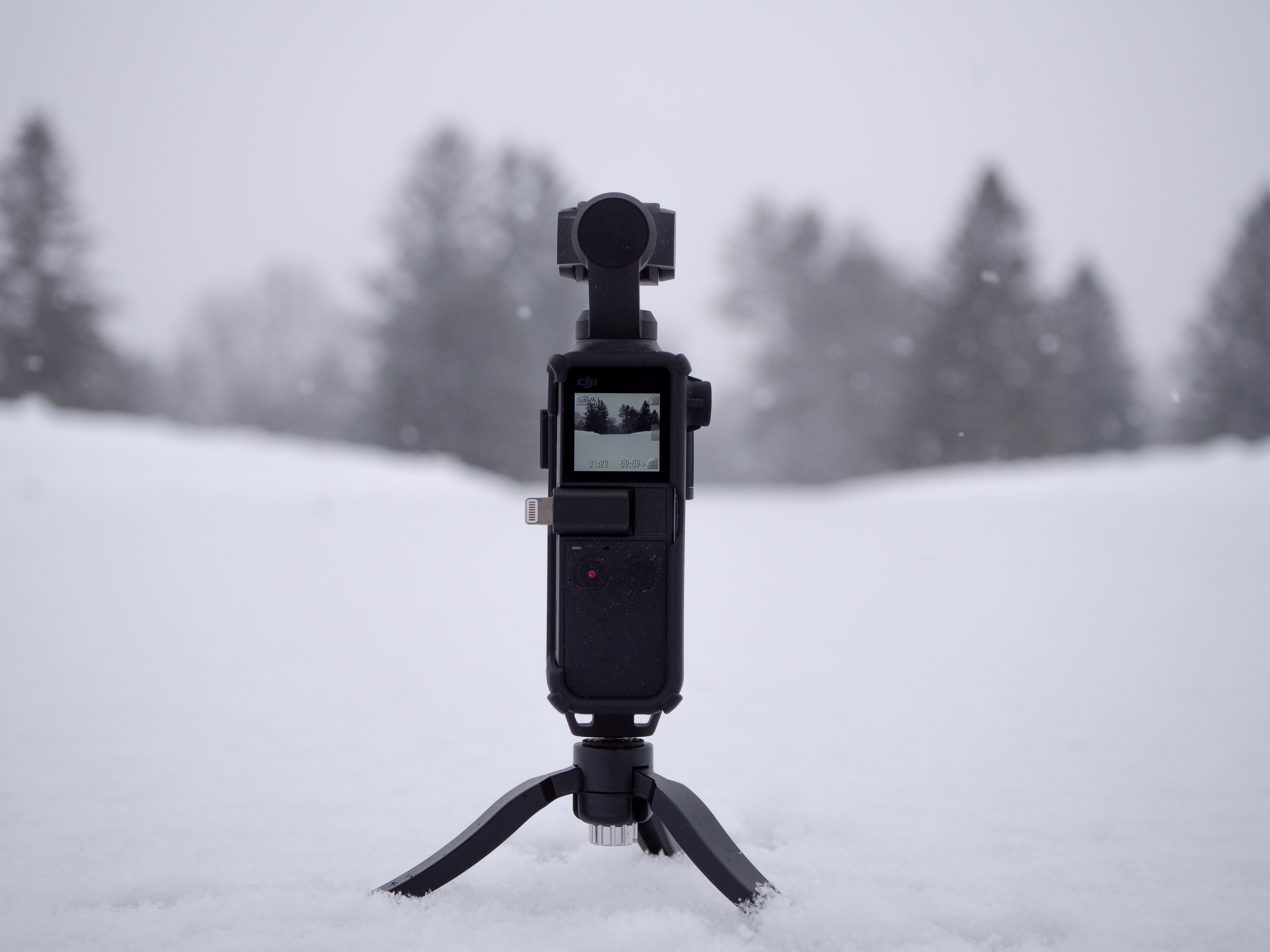 black camera with stand on snow field