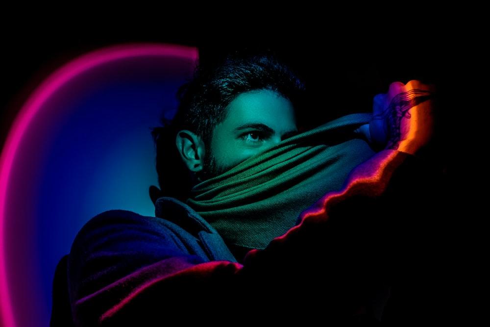 man hiding face with grey textile