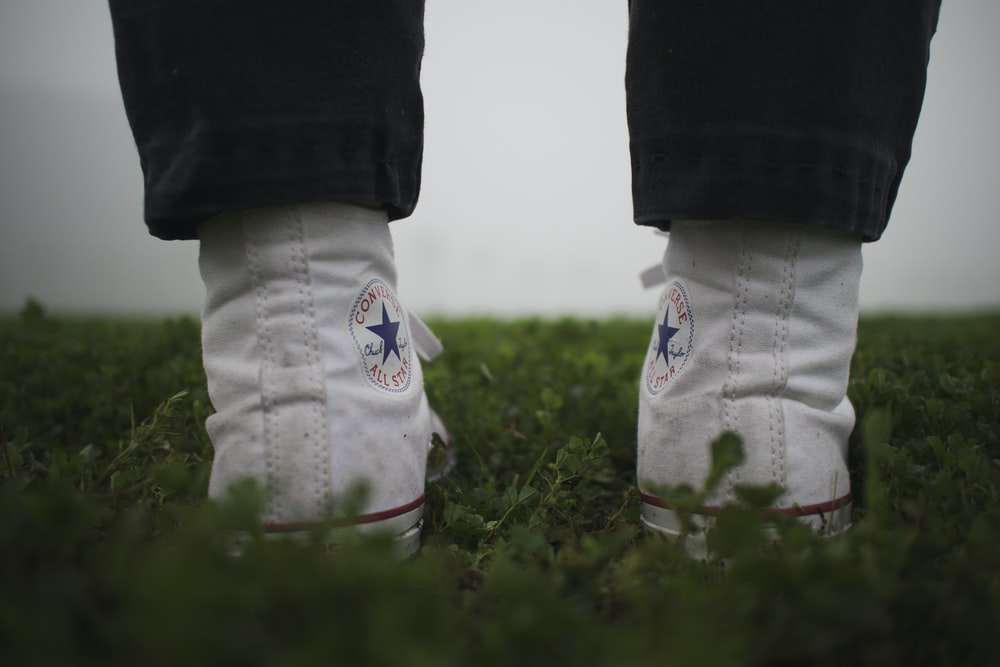person wearing pair of white Converse high-top sneakers
