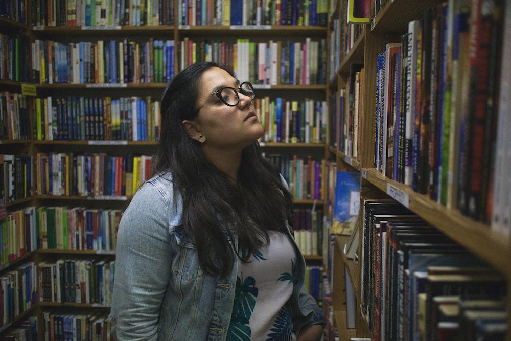 woman in blue chambray dress shirt standing near bookshelf