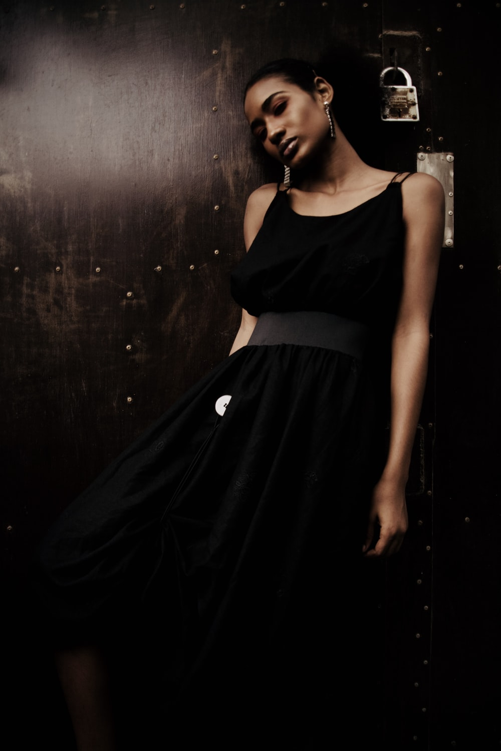 woman in black sleeveless dress leans on wall