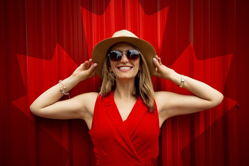 woman in red sleeveless top holding her hat while smiling