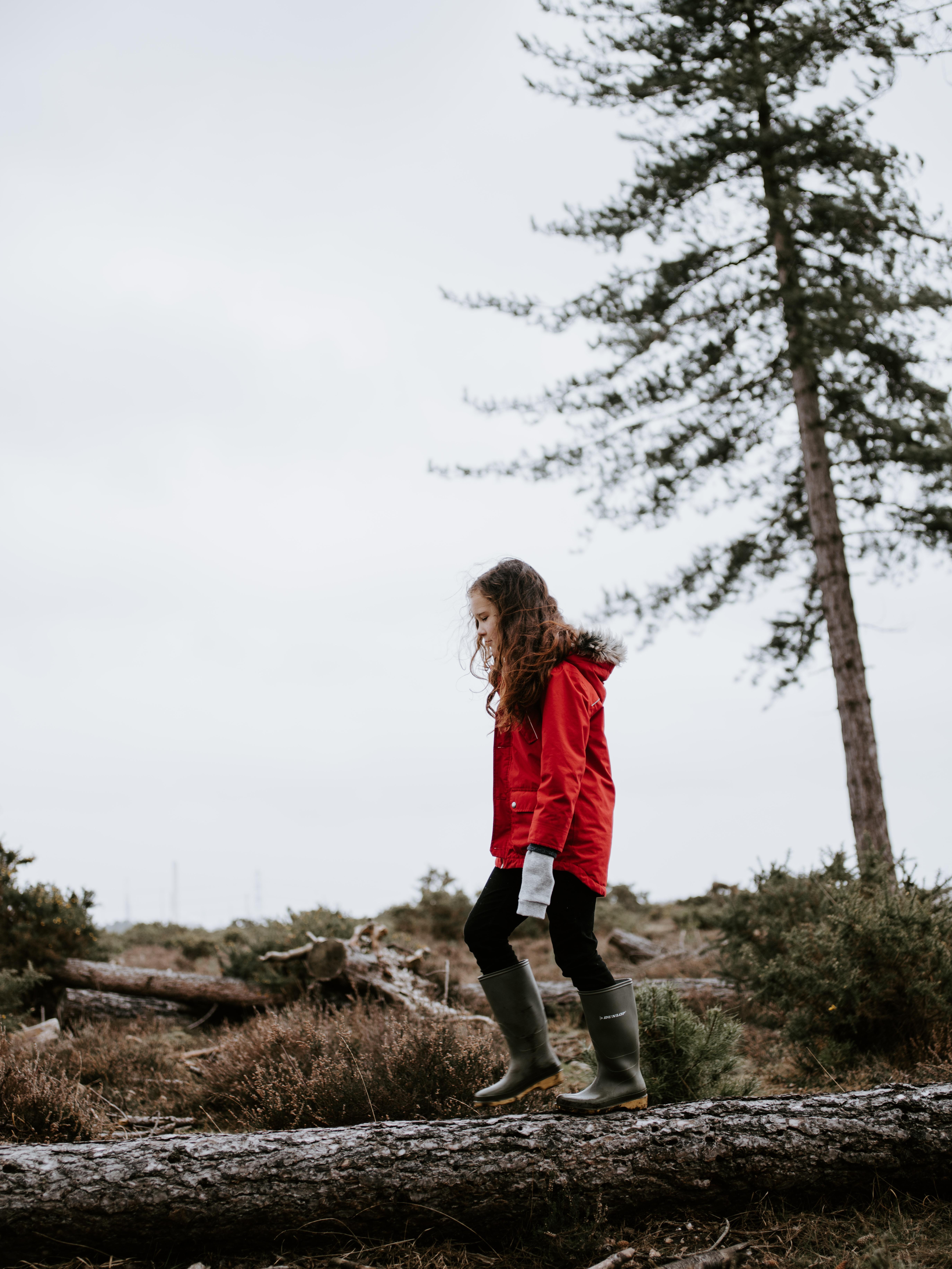 girl in parka walking on tree trunk
