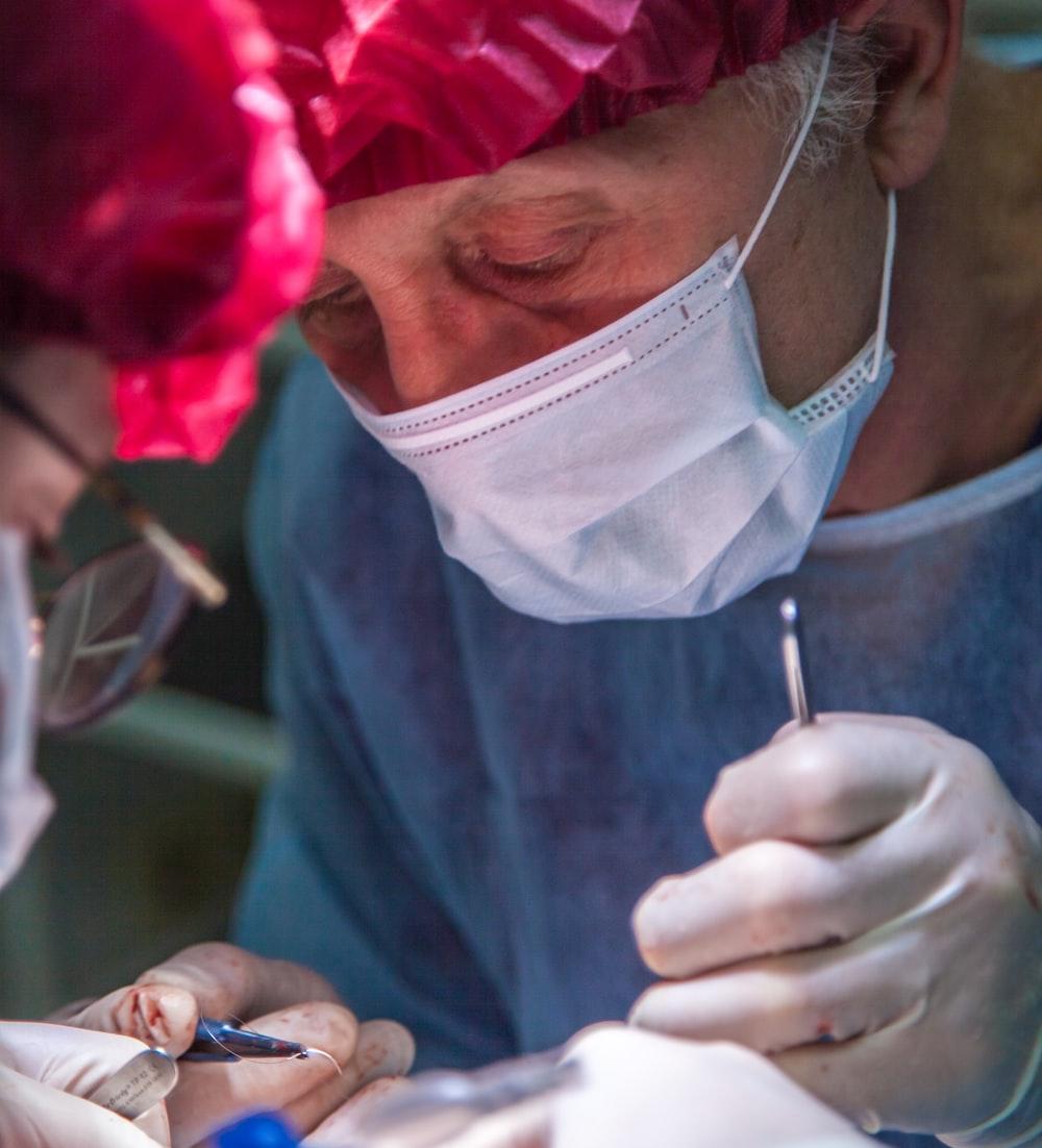 surgeon wearing white mask and pink hat